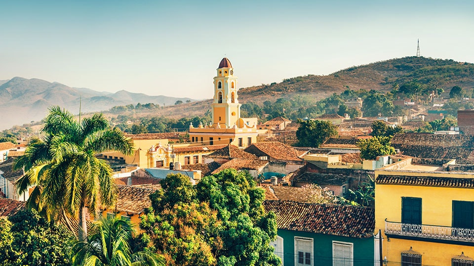 Panoramic view over the city of Trinidad, Cuba, with mountains in the background and a cloudy sky