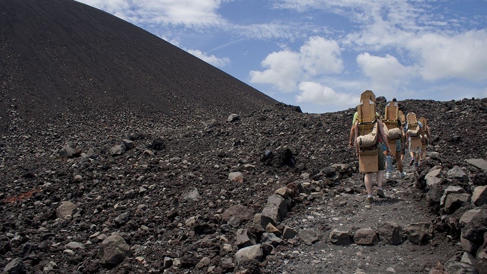 A group of tourists climbing the Volcano Cerro Negro with their boards on the way to volcano board back down it.